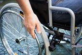 stock photo of wheelchair  - Paralyzed man using his wheelchair - JPG
