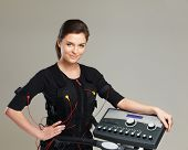 image of stimulating  - Young woman in training costume near Electro Muscular Stimulation EMS machine - JPG