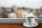 stock photo of rainy weather  - Coffee cup against window with rainy day view - JPG