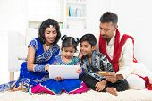 stock photo of ebusiness  - Indian Asian family using tablet pc computer online shopping with credit card at home - JPG
