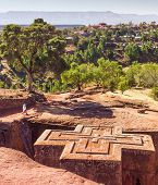 image of rock carving  - An Ethiopian woman walks near the top of St George church at Lalibela in Ethiopia - JPG