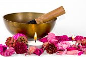 foto of tibetan  - Studio shot of a tibetan bowl some pink flowers and candles over white background - JPG