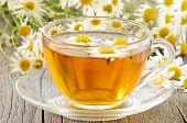 foto of chamomile  - Herbal chamomile tea with chamomile flowers on wooden table