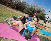 stock photo of lady boots  - Boot camp fitness class working out on mats outdoors - JPG