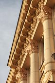 foto of neoclassical  - Fragment of classic or neoclassic building with columns and fine capitals illuminated with warm summer sunlight blue sky visible - JPG