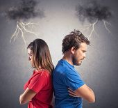 stock photo of disappointed  - Problem of a young couple with blacks clouds and lightning - JPG