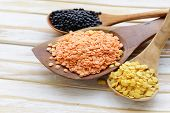stock photo of legume  - different kinds of lentils - red, yellow and black in wooden spoons