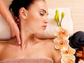stock photo of low-necked  - Masseur doing massage the neck of an adult woman in the spa salon