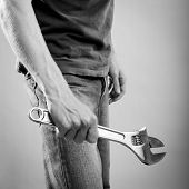 image of adjustable-spanner  - A young man dressed in casual clothes holds a large adjustable wrench or spanner - JPG