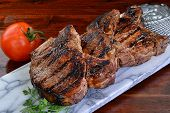 stock photo of slab  - Thick two inch pork chops on a marble slab - JPG
