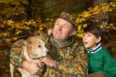 stock photo of laika  - Grandfather grandson and dog hunting in the autumn forest - JPG