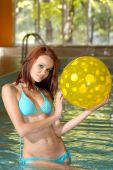 foto of poka dot  - closeup portrait of sexy brunette holding a yellow poka dot beach ball - JPG
