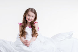 foto of nighties  - Adorable happy little girl in pink nightie awake and sitting on the bed  - JPG