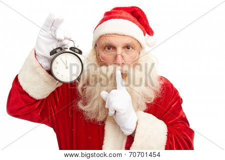 Santa Claus with alarm clock showing five minutes to midnight making shhh gesture and looking at camera