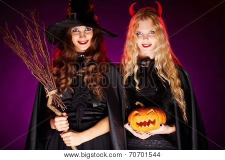 Two young women with broom and pumpkin looking at camera with smiles