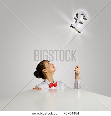 Young woman holding balloon shaped like pound sign