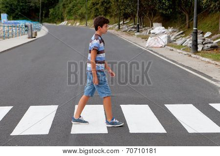 Teenager through a zebra crossing in his town
