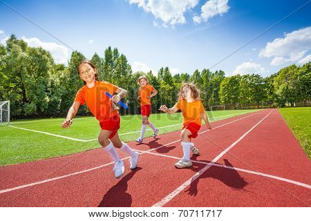 Three girls with one relay baton running