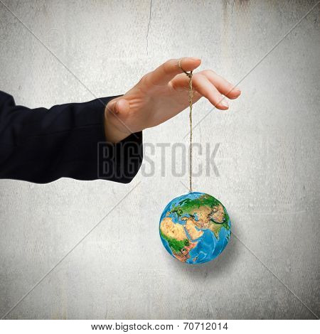 Close up of human hand holding Earth planet on rope. Elements of this image are furnished by NASA
