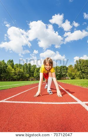 Boy ready to run with two straight arms on ground