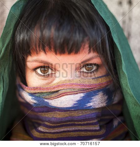 Close-up portrait of young girl covers her face with a veil. Hijab.