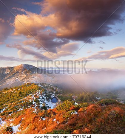 Autumn landscape in the mountains. First snow on the slopes. A small lake is covered with ice