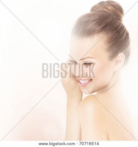 Young Beautiful Woman Touching her Face. Pretty model girl Touching her Cheek. Sideways portrait of skincare. Woman with well-groomed skin. Spa and Skin Care Concept.
