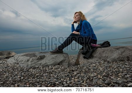 Pensive/dreaming woman on the beach