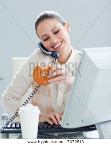 Confident Businesswoman On Phone Eating A Donnut