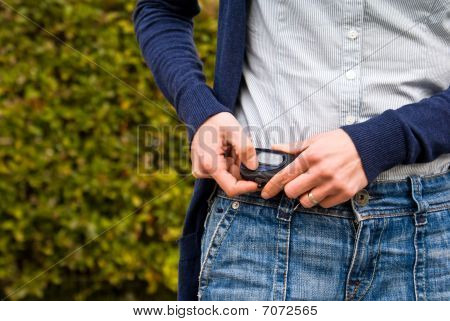 A Woman Checks Her Pedometer While Walking Outdoors