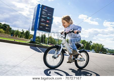 Cute Little Girl Riding Fast By Bicycle