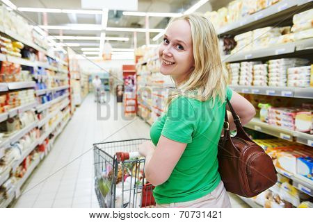 Shopping. Woman with shopping cart trolley in store or supermarket
