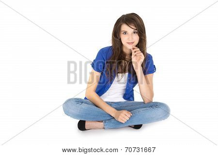 Isolated Young Smiling Teenager Sitting In Crossed Legs On The Ground.