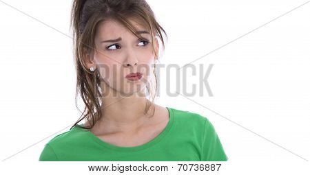 Face Of A Skeptical Young Woman In Green Shirt Isolated.
