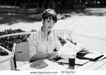 Young business woman working at sidewalk cafe