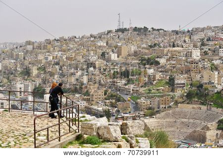 AMMAN, JORDAN - MARCH 17, 2014: Tourists admire the view to the Roman Theatre from the Citadel hill. Built in the II century, it could seat about 6,000 people