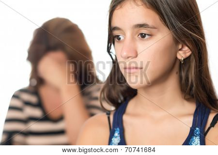 Teenager problems - Sad teenager with a serious expression and her mother crying on the background