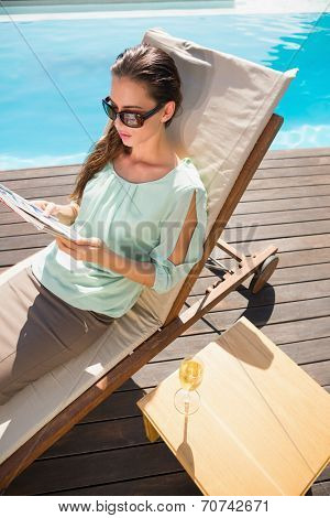 Side view of young woman reading book by swimming pool with champagne on table