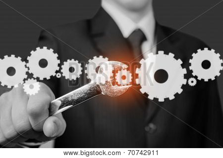 Businessman holds wrench with cogwheels