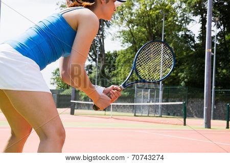 Tennis player standing on court on a sunny day