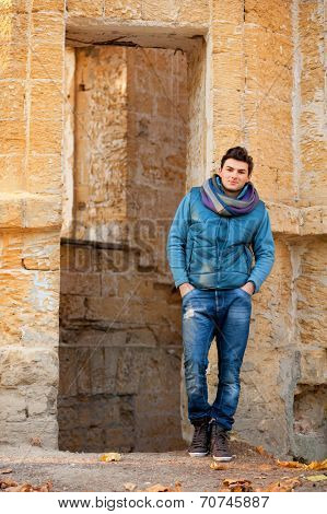 Young handsome man posing against grunge ruins.