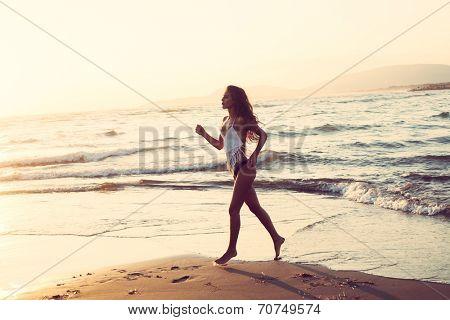 young woman run along sandy beach at sunset, full body shot