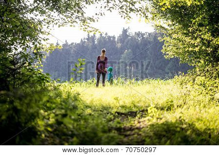Mother And Child Walking In Lush Green Countryside