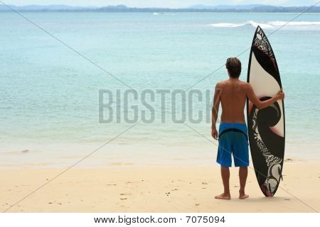 Surfer Standing On Beach With Funky Arty Surfboard