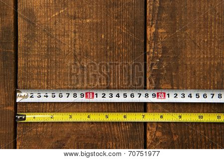 Inch measure and metric measure side by side, on a wooden work table. starting point is the same position.