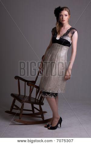 Atractiva joven de pie junto a una silla mecedora