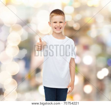 advertising, gesture, people and childhood concept - smiling little boy in white blank t-shirt showing thumbs up over holidays background