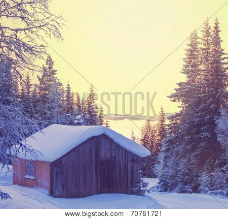 wooden hut in the mountains at winter