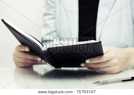 Business woman reading a notebook