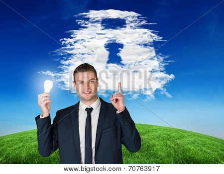 Composite image of businessman holding light bulb and pointing against cloud lock